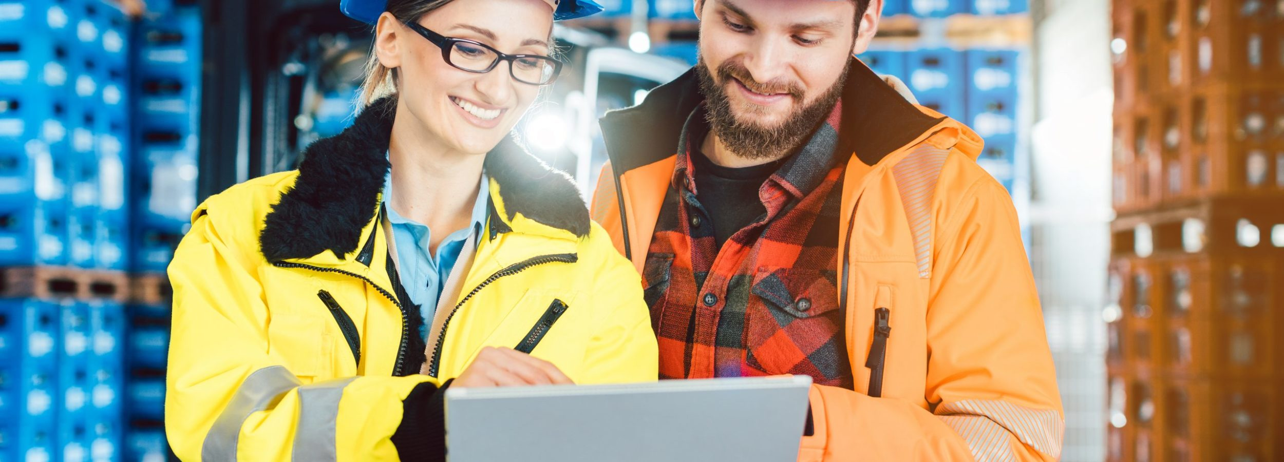 Woman and man as workers in logistics center using computer checking data